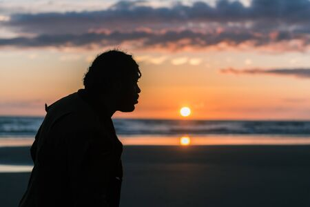 A silhouette of black male man with dreadlocks on a sunny beach with a sunset. Thinking and clarity in the great outdoors. Walking and fresh air for good positive mental health
