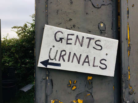 a Hand made dirty sign directing people at festivals to the mens restroom toilets. Dirty toilets and unhygienic lavatories at events spreading viruses and bacteria.