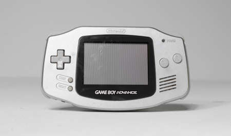 london, england, 26/06/2020 A retro hand held nintendo gameboy silver game boy advance, front on angle, isolated on a white studio background. Nintendo vintage famous iconic portable video game device.