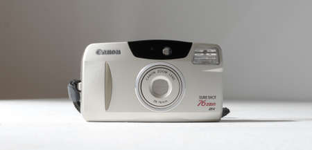 london, england, 05/05/2019  a retro vintage 1990s canon sure shot 76 zoom AF 35 mm film camera isolated on a white background. kodak lens, old photographic technology