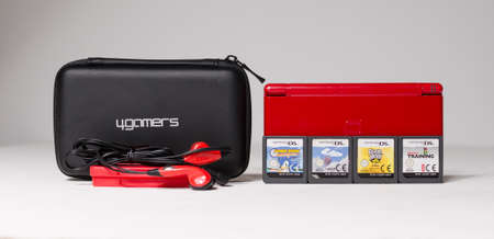 london, uk 05/05/2020A A gloss red nintendo ds lite hand held vintage console bundle, case and games on a white studio background. Retro video gaming handset. nostalgic video gaming
