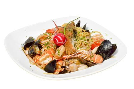 Seafood pasta spaghetti with clams, prawns, sea scallops on white plate on white background Stock Photo