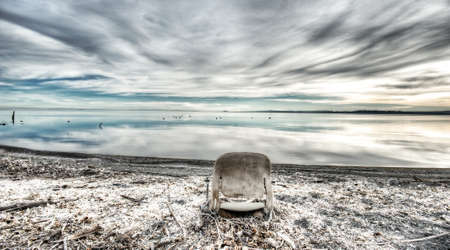 broken chair: Old, broken chair sitting on the beach next to the water with beautiful clouds reflecting off the water