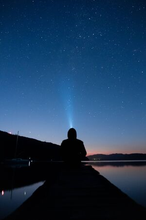 Man gazing over the night sky with the flashlight