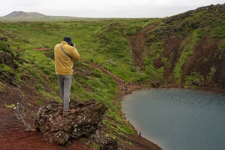 Man in the yellow jacket photographing in Iceland Banco de Imagens - 138271557