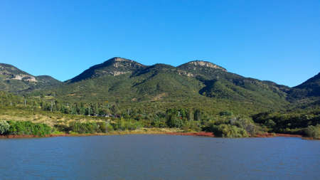 lake on the shore of the mountain on sunny day Banco de Imagens