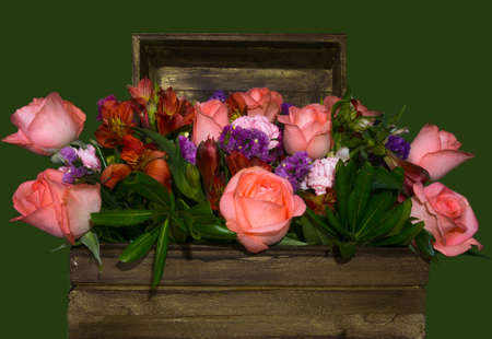 Bouquet of flowers inside a wooden chest whit green background