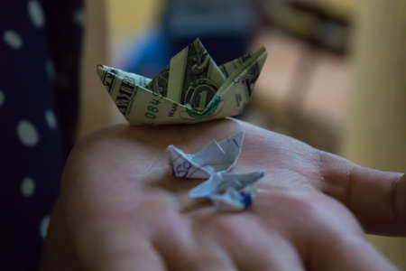 three paper boats, and a boat made with a dollar bill, on one hand