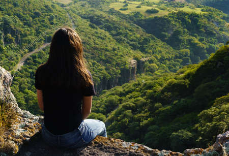 teenager sitting on the shore of a cliff looking down Banco de Imagens