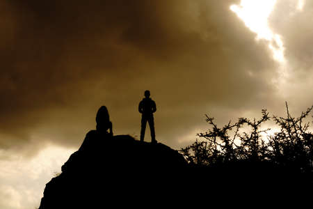 silhouettes on top of a mountain with an epic sky