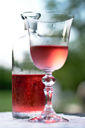 A small bottle and a glass of cold, rose wine on a table with a white cloth on it, half full, with water droplets formed on them due to condensation.
