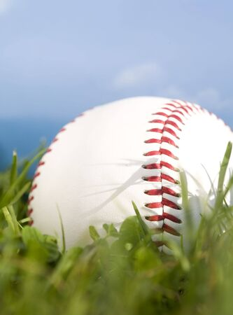 close up: Summer baseball concept with a baseball in the outfield grass against a perfect blue sky. Stock Photo