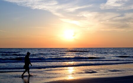Silhouette of man walking along beach at sunset Stock Photo - 8079038