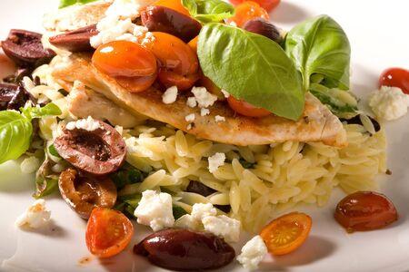グルメとフェタチーズ、チェリー トマト、カラマタ オリーブ、新鮮なバジルの米のベッドの上の鶏の健康的な夕食。