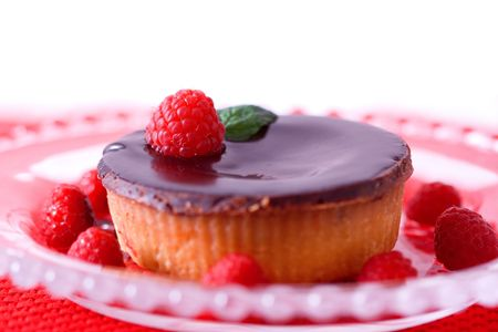 A gourmet chocolate raspberry tart dessert on glass dish. Stock Photo