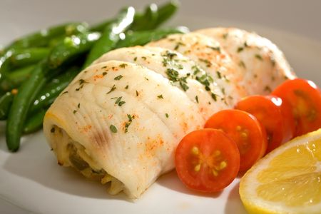 stuffed fish: Gourmet dinner of crab stuffed flounder with cherry tomatoes and green beans.