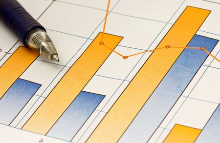 A pen composed over a business chart of earnings trends. photo