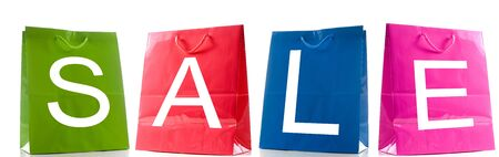 consumerism: Colorful shopping bags spelling out Sale. Isolated against a white background. Stock Photo