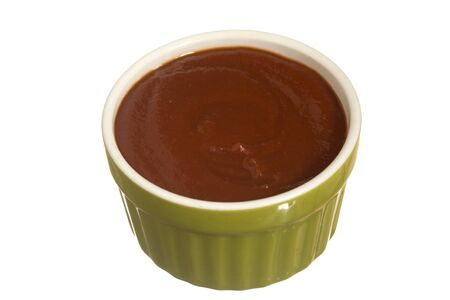 Organic ketchup served in a ramekin bowl. Isolated with clipping path included.