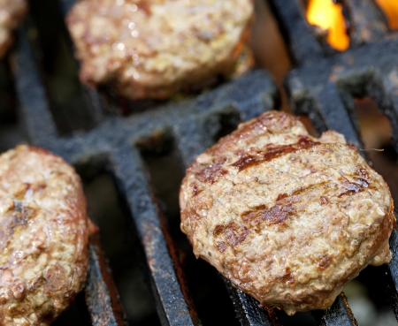 grates: Slider hamburgers cooking on a barbecue grill.