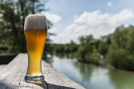 near beer: A glass of beer on the terrace near by a lake