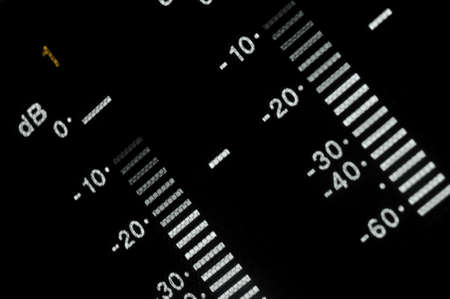decibels: Perspective macro shot of the equalizer display of the professional digital betacam recorder. Shallow dof. Visible data: sound scale, decibels, meters with gray gradation, white and red digits