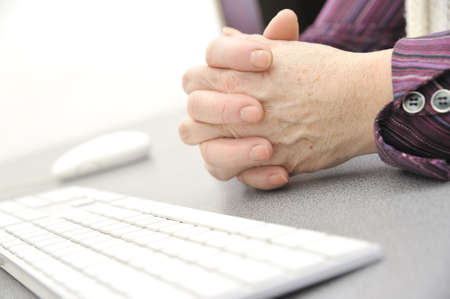 Hands of an old female typing on the keyboard, isolated on white, close-up. Stock Photo - 11937376