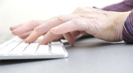 70s adult: Hands of an old female typing on the keyboard, isolated on white, close-up.