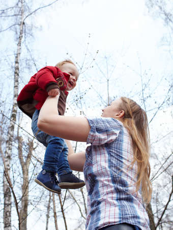 two year old: Happy young mother and her son laughing and playing together in the park on the sky background.