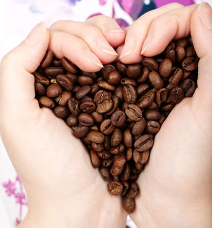 Heart of cofee grains in hands. Natural morning light. photo