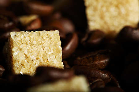 Brown sugar cube and coffee beans background. Natural morning sunlight. photo