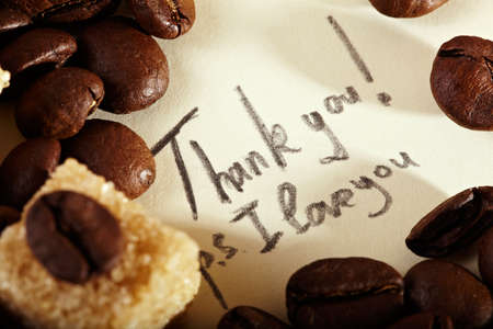 Coffee beans on yellowish vintage paper with pencil inscription: Thank you, I love you. Natural morning sunlight. photo