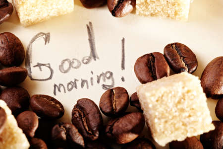 Coffee beans on yellowish vintage paper with pencil inscription: Good morning. Natural morning sunlight. photo