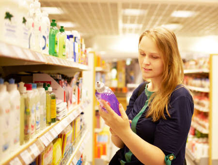 Young woman in the supermarket reading inscription Фото со стока - 14633166