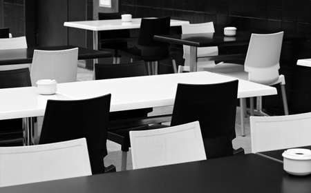 Black and white tables and chairs. A street small cafe. photo