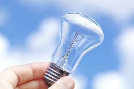 incandescent: An incandescent lamp against the blue sky with clouds. Stock Photo