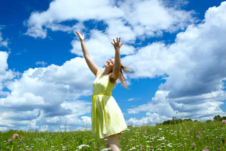 A young happy girl with streaming in the wind hair, in a yellow dress, is throwing in the air camomile petals and smiling. Freedom concept. photo