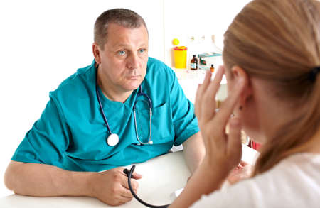 consultant physicians: A young girl is complaining of headaches  A light medical study  The doctor of 45-50 years old in a green smock  Caucasian  Shallow depth of field  Focus is on the doctor  Stock Photo