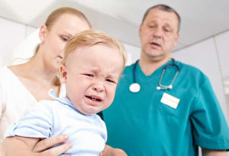 A 1,5 year-old boy is frightened and crying in a medical study  The doctor and the baby's mother are at a loss  Shallow dof  Focus is on the boy  photo