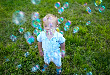 A little 16 month-old boy is looking at soap-bubbles  Baby s dreams Stock Photo - 15247040