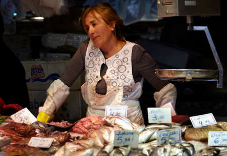 BARCELONA - MAY 26  The market fish monger tired lady stays at counter and smiles on May, 26, 2012 in city market in Barcelona, Spain