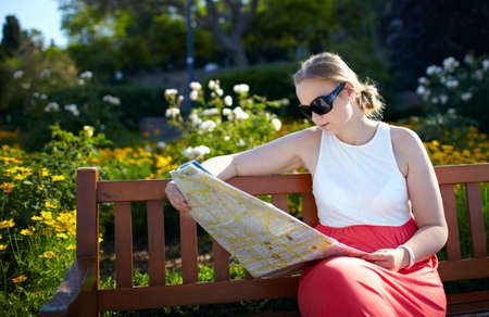 25 years old girl in sunglasses is reading the map sitting on the bench in the park photo