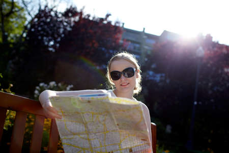 against the sun: 25 years old girl in sunglasses is reading the map sitting on the bench in the park  Shot against sun  Stock Photo