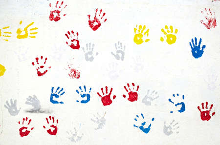 Graffiti with multiple colored hand prints on the white wall background  photo