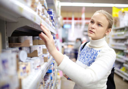 purchaser: Young woman is choosing food for her child in the supermarket  Stock Photo