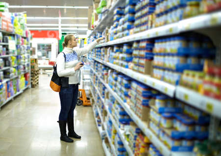 merchandiser: Young woman is choosing food for her child at the food store  Wide shot, shallow dof  Stock Photo