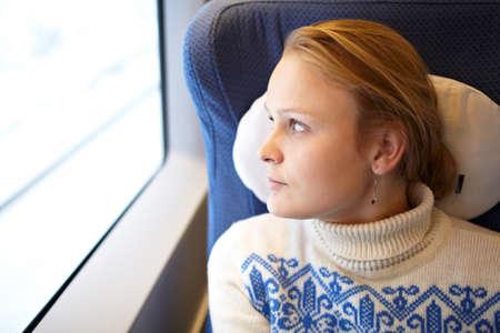 visage femme profil: Jeune femme regarde des scènes de fenêtres et de penser dans le train à grande vitesse modernes Banque d'images