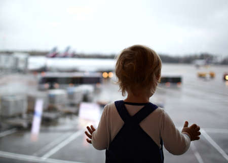 Two year old babyboy is looking at the planes in the airport  Фото со стока