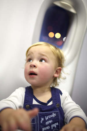 baby on chair: Young passenger in the plane  Beautiful bokeh lights in the porthole