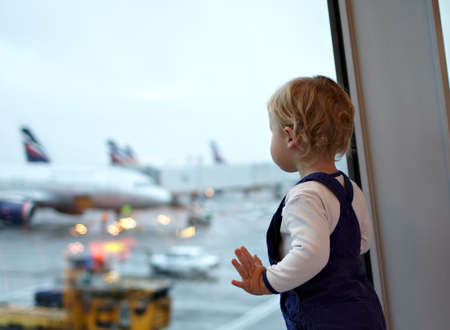 interested baby: Kid near the window in the airport  Stock Photo